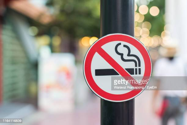 close-up of no smoking sign on pole - no smoking sign stock pictures, royalty-free photos & images