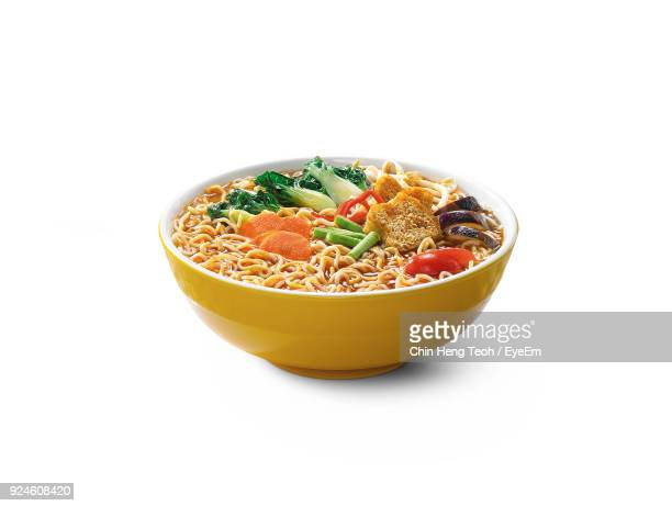 close-up of noodles in bowl against white background - noodle foto e immagini stock