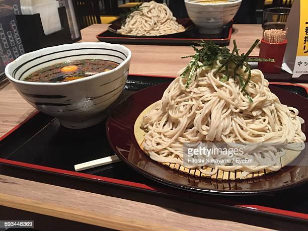 Close-Up Of Noodles Served In Plate By Bowl Of Curry On Table