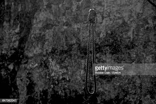 close-up of noose hanging against rock - suicide stock photos and pictures