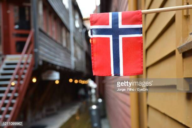 close-up of norwegian flag against buildings in city - filho stock pictures, royalty-free photos & images