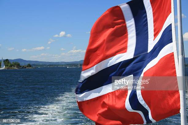 close-up of norwegian flag against sea - norwegian flag stock pictures, royalty-free photos & images