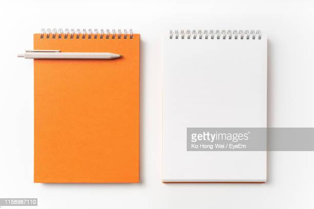 close-up of note pad and pen against white background - note pad stock pictures, royalty-free photos & images