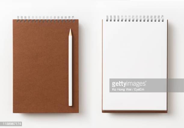 close-up of note pads and colored pencil against white background - spiral notebook stock pictures, royalty-free photos & images