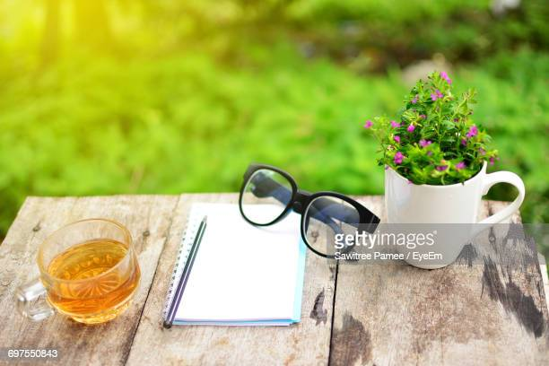 Close-Up Of Notebook And Reading Glasses On Table