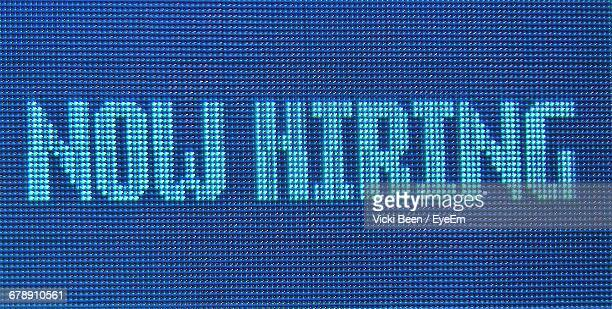 close-up of now hiring neon sign - help wanted sign stock photos and pictures