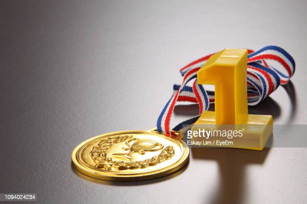 close-up of number 1 with gold medal on gray background - gold medalist stock pictures, royalty-free photos & images