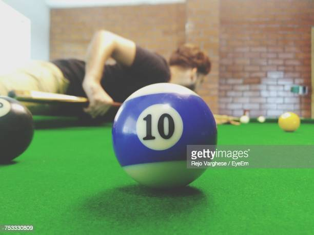 Close-Up Of Number 10 On Pool Ball While Man Playing In Background