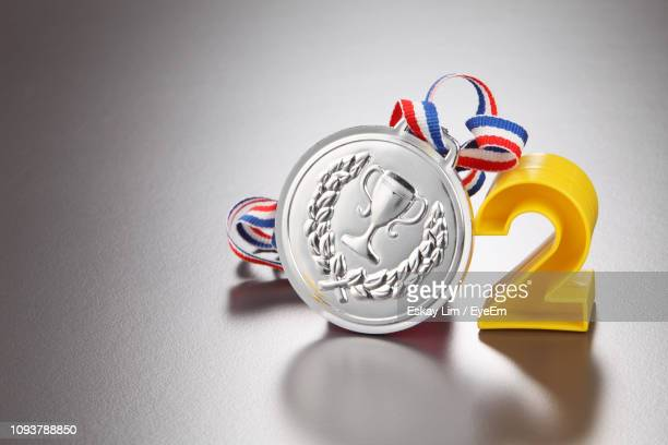 close-up of number 2 with silver medal on gray background - number 2 stock pictures, royalty-free photos & images