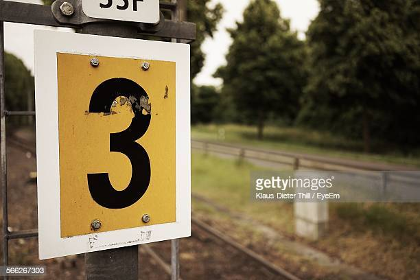 Close-Up Of Number 3 On Pole Near Railroad Tracks