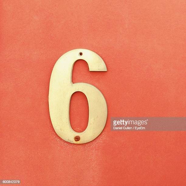 Close-Up Of Number 6 On Orange Wall