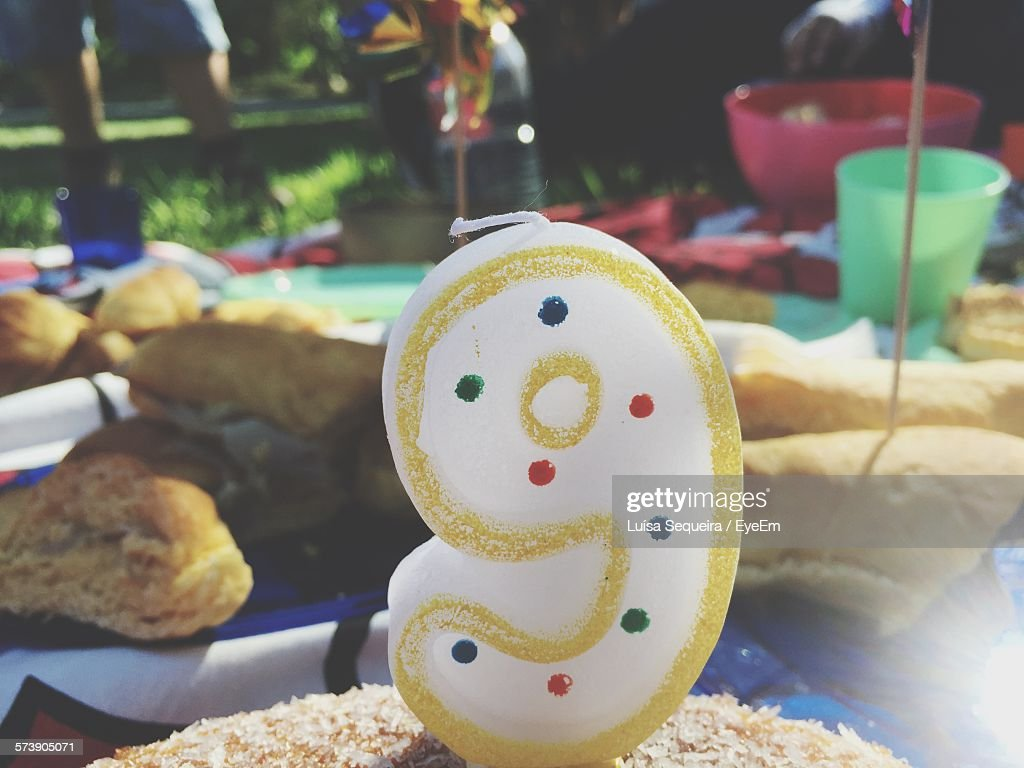 Close Up Of Number 9 Birthday Candle On Cake Stock Photo
