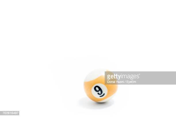Close-Up Of Number 9 On Pool Ball Against White Background