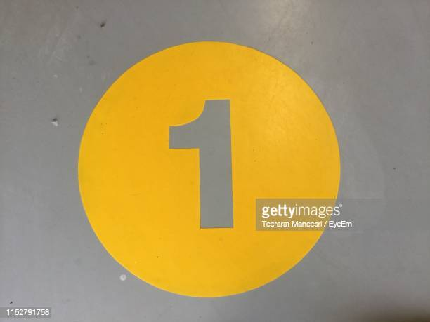 close-up of number in yellow circle on wall - number 1 stock pictures, royalty-free photos & images