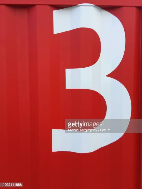 close-up of number on red wall - number 3 stock pictures, royalty-free photos & images