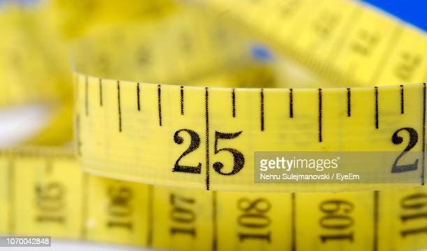 Close-Up Of Number On Yellow Tape Measure At Table