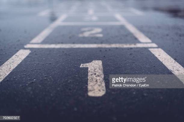 close-up of number one on asphalt - hopscotch stock pictures, royalty-free photos & images