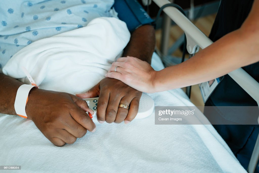 Close-up of nurse touching senior patients hand in hospital ward : Stock Photo