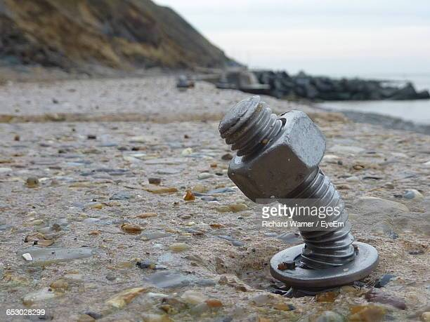 Close-Up Of Nut And Bolt On Rock At Beach