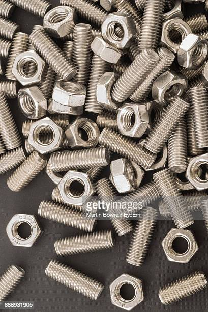 close-up of nuts and bolts on table - nut fastener stock photos and pictures
