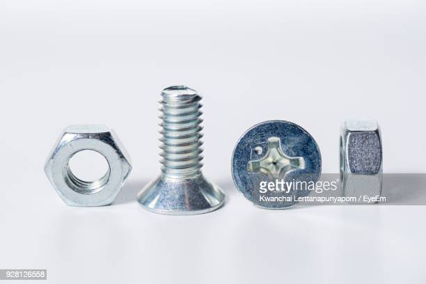 Close-Up Of Nuts And Bolts Over White Background