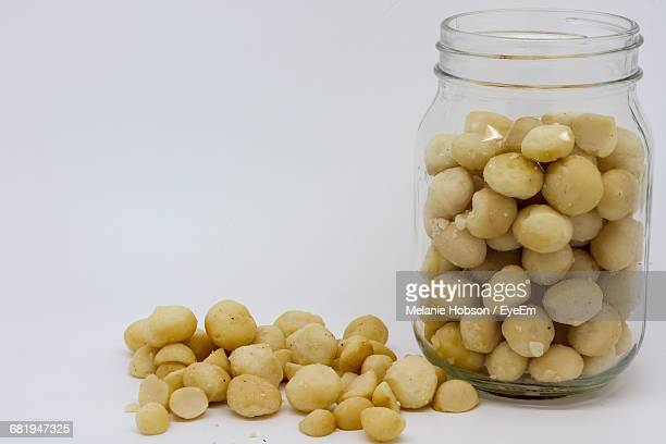 close-up of nuts by glass container - macadamia nut stock photos and pictures