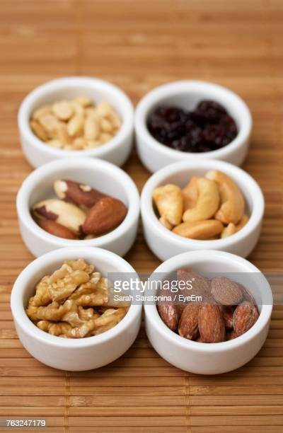 close-up of nuts in bowls on wooden table - brazil nut fotografías e imágenes de stock