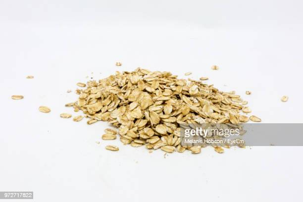 close-up of oat flakes on white background - rolled oats stock photos and pictures