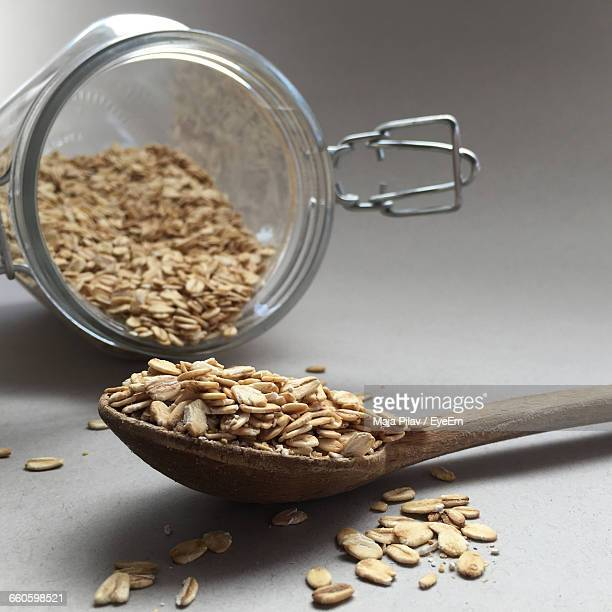 Close-Up Of Oats In Spoon And Glass Container On Table