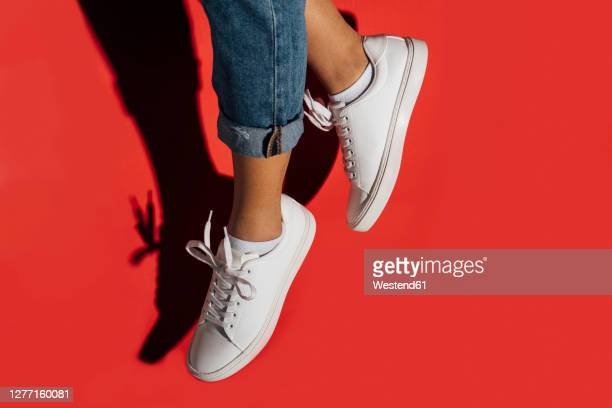 close-up of of female wearing sneakers while jumping against red background - footwear stock pictures, royalty-free photos & images