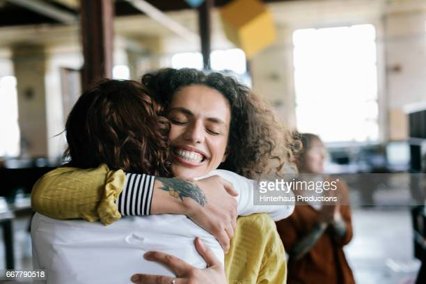 closeup of office workers hugging - adulte d'âge moyen photos et images de collection