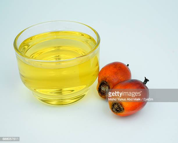 Close-Up Of Oil And Palm Fruits Against White Background
