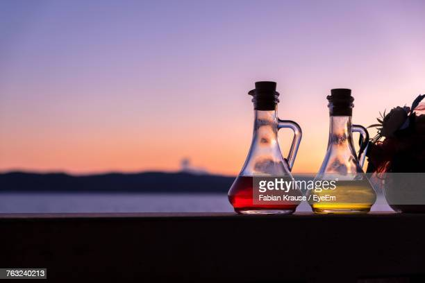 Close-Up Of Oil And Vinegar Bottle In Restaurant At Sunset
