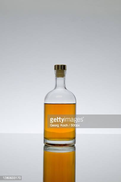 close-up of oil in bottle against white background,austria - images stock-fotos und bilder