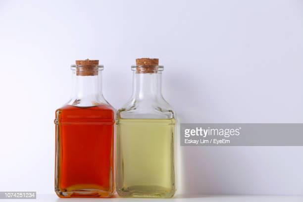 close-up of oil in bottles on table against white background - palm oil stock pictures, royalty-free photos & images