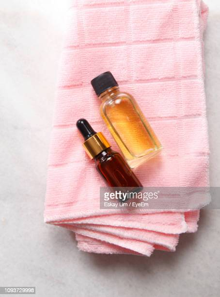 close-up of oil in bottles on towel - essential oil stock pictures, royalty-free photos & images