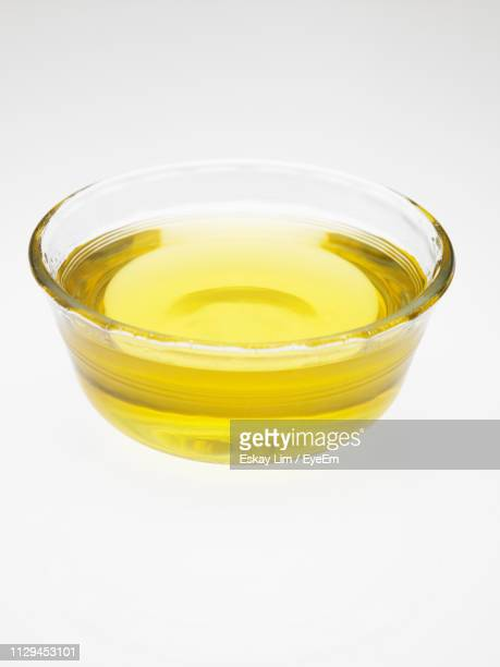 close-up of oil in container against white background - olive oil stock pictures, royalty-free photos & images