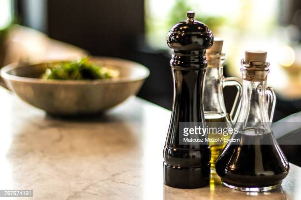 close-up of oil in jar with salt shaker on table - salt and pepper shakers stock pictures, royalty-free photos & images