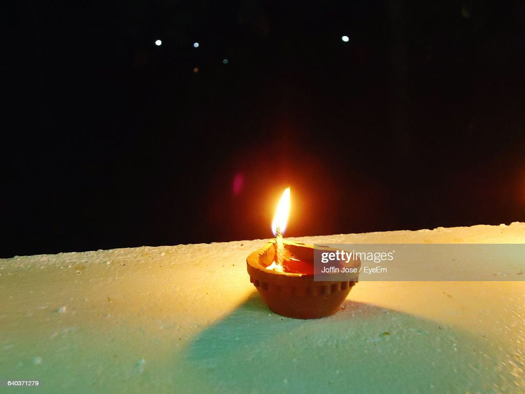 Close-Up Of Oil Lamp On Wall At Night : Stock Photo