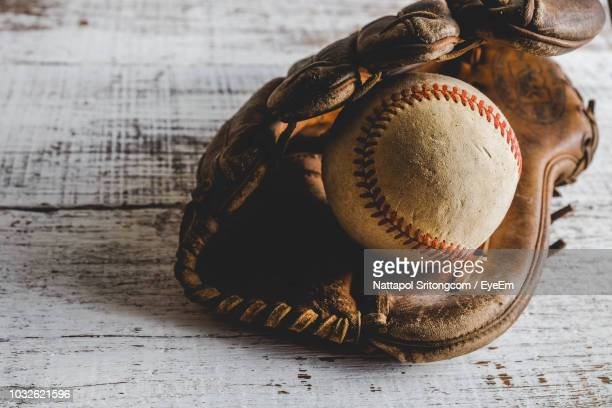 close-up of old ball in leather glove on table - baseball glove stock pictures, royalty-free photos & images