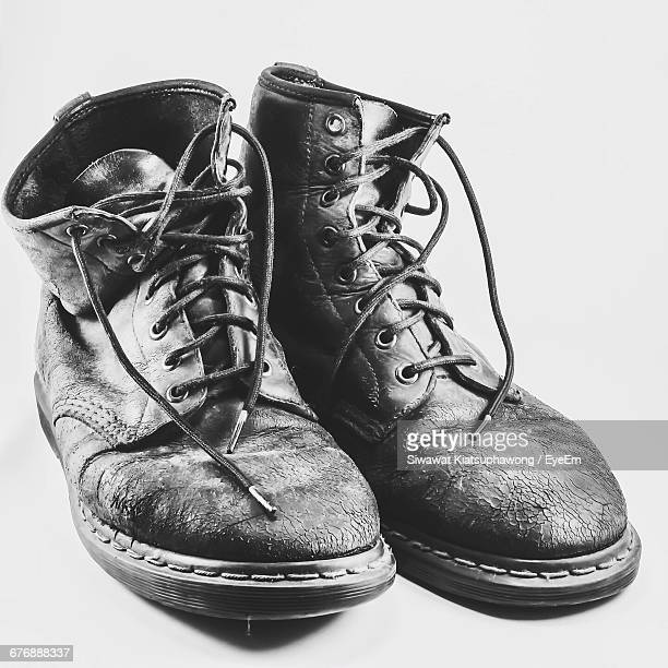 Close-Up Of Old Boots On White Background