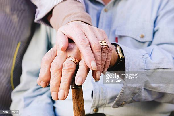Close-up of old man's and woman's hands resting on a cane