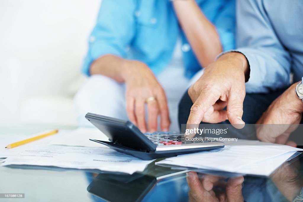Closeup of old man's hand calculating bills at home : Stock Photo
