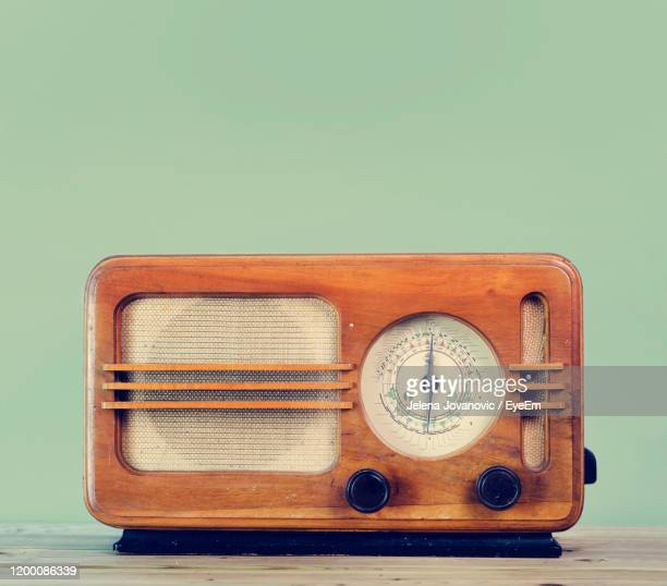 close-up of old radio on table against green background - radio stock pictures, royalty-free photos & images