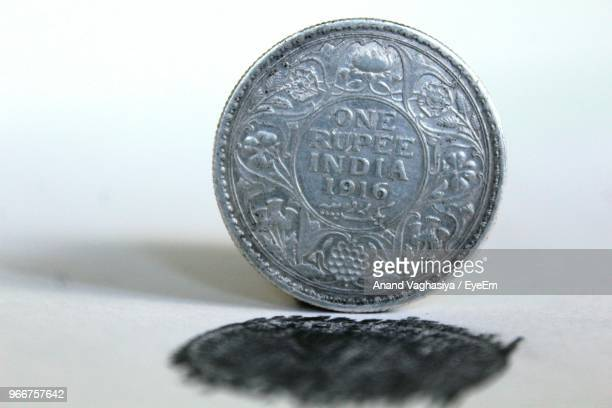 Close-Up Of Old Rupee Coin On White Table