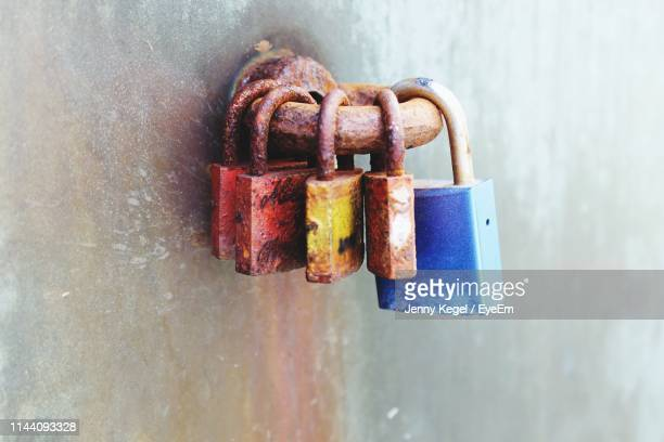 Close-Up Of Old Rusty Padlocks Hanging On Metal