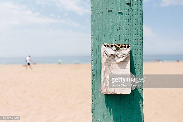 Close-Up Of Old Torn Note Pad On Wood At Beach