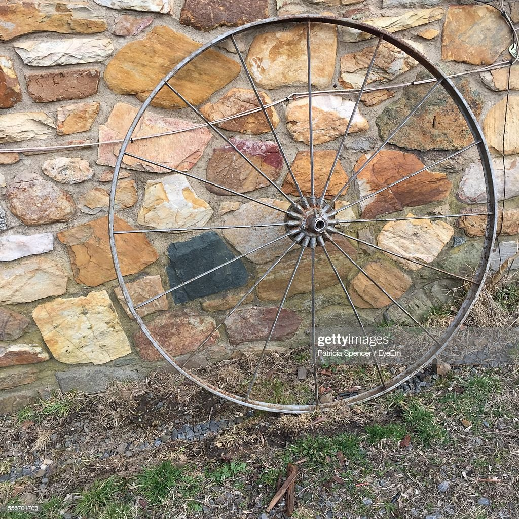 Closeup of old wheel against stone wall stock photo getty images close up of old wheel against stone wall stock photo publicscrutiny Choice Image