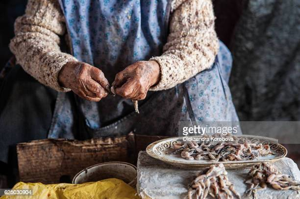 Close-up of old woman's hands peeling frog legs for sale in the market in Cusco.