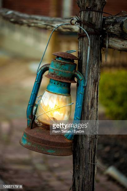 close-up of old-fashioned lantern hanging from wooden railing - florin seitan stock pictures, royalty-free photos & images